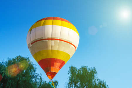 Photo pour Colorful hot air balloon is flying in the blue sky above the trees. - image libre de droit