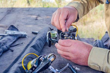 Photo pour a man repairs a fishing reel with improvised means. - image libre de droit