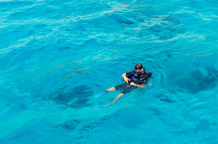 Photo pour Sharm El Sheikh, Egypt, May 8, 2019: A man in diving equipment swim in the clear blue water of the sea. - image libre de droit