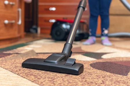 Photo pour A small child vacuums a carpet with a vacuum cleaner. - image libre de droit