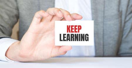 Photo pour businessman holding a card with text KEEP LEARNING - image libre de droit