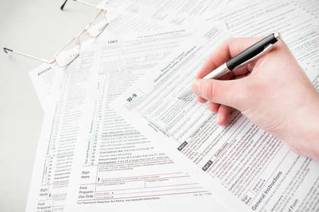 Photo pour Close up of male accountant filling tax form. Man writing something sitting at his office. Filling individual income tax return form 1040, making financial report, home finances or economy concept - image libre de droit