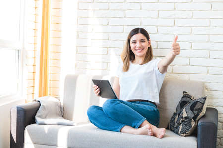 Foto de Technology, internet and people concept - happy attractive woman with tablet computer showing thumbs up at home - Imagen libre de derechos