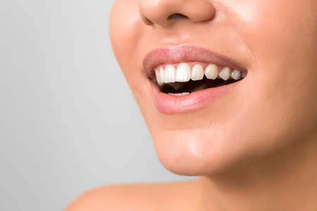 Photo pour wide and beautiful smile of a young woman with clean skin and white teeths against grey background - image libre de droit