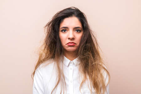Photo pour sad woman with tangled hairs in white shirt against pink background. morning womans routine - image libre de droit