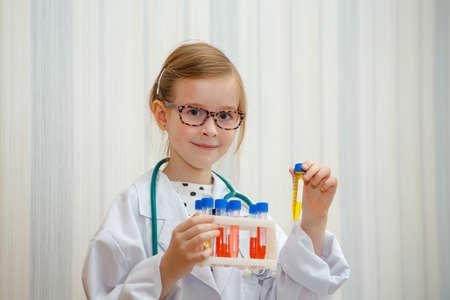 Foto de Little girl in a doctor s smock examines test tubes with tests. Educational medical game. - Imagen libre de derechos