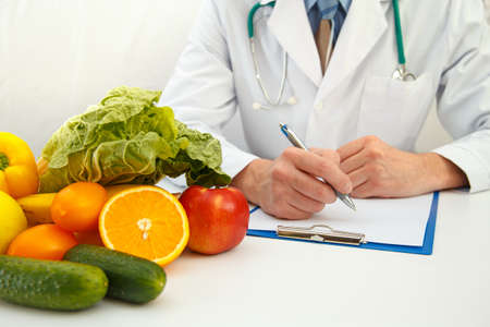 Photo for Nutritionist doctor writing diet plan on table. Right nutrition and slimming concept - Royalty Free Image