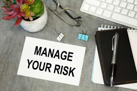 Foto de MANAGE YOUR RISK- lettering on paper on the desktop, notepad, pen and keyboard. Concept photo of the advantage. - Imagen libre de derechos