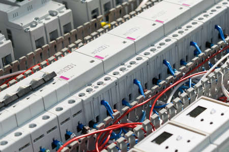 A series of modular magnetic contactors and a range of power circuit breakers. Between the rows of contactors and switches and devices, perforated cable channels. They laid the electrical wire.