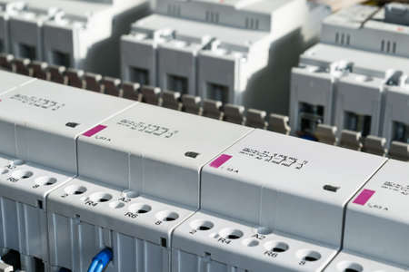 A series of modular magnetic contactors and a range of power circuit breakers. Between the rows of contactors and switches, perforated cable channels. To the contactor of the connected wires.
