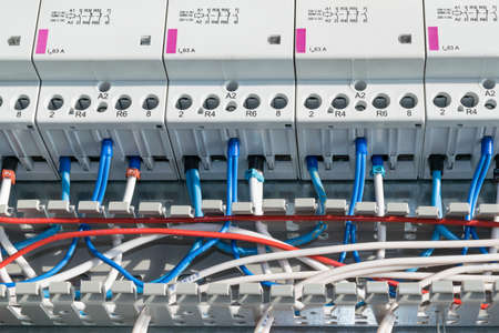 A number of modular contactors, cable channel and wire. Wire laid in the cable channel and connected to the modular contactors in electrical Cabinet. The wires from the terminals and marking.