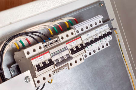 A series of modular circuit breakers in an electrical Cabinet with electrical wires or cables connected to them. The wires are color-coded. The modern distribution of electricity.