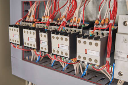 A series of magnetic starters or contactors with additional contacts and electrical wires connected to them in an electrical Cabinet. The wires are connected according to the project.