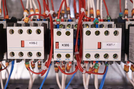 Three contactors or magnetic starters with front contacts are arranged in a row in the electrical Cabinet. Wires and cables are connected to the contactors and front contacts. Production, maintenance.