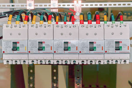 Photo for The number of high-power electric circuit breakers molded case circuit breakers in an electrical closet. Electrical cables or wires are connected to the switches. The cables are marked with color. - Royalty Free Image