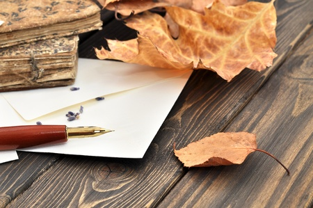 Fountain pen on empty letter with autumn leaves and old books on a wooden table