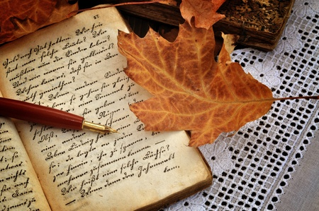 Photo pour Fountain pen on old handwritten book with autumn leaves on a lacy tablecloth - image libre de droit