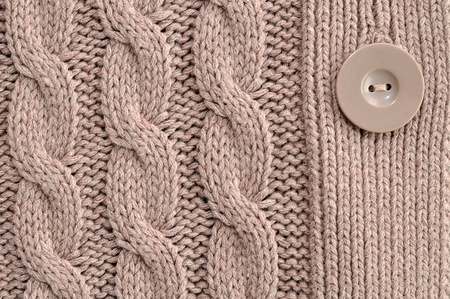Brown knitted woolen background with button