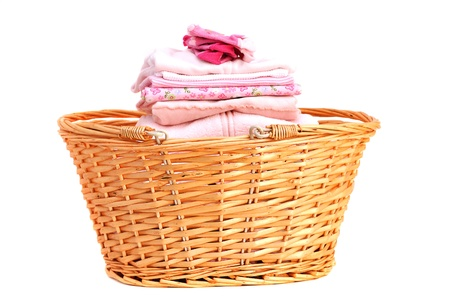 Folded pink baby laundry in a wicker basket, isolated on white