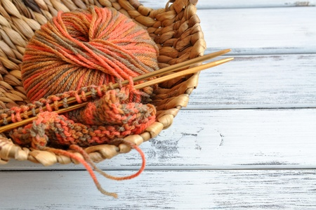 Knitting needles and yarn in autumn colors in a wicker basket