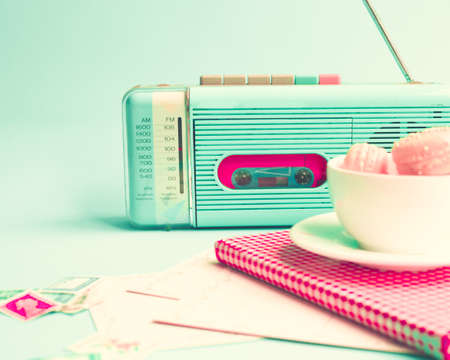 Pink macaroons in a coffee cup and vintage radio