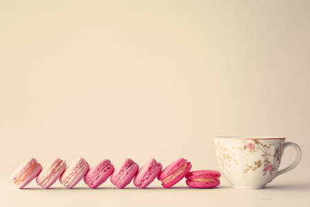 Line of macaroons and vintage tea cup