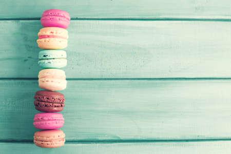 Photo pour Colorful macaroons over turquoise wood - image libre de droit