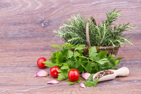 Fresh rosemary, parsley with oil on wooden  background