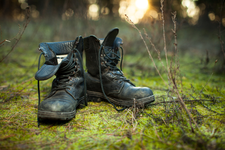Foto de Old leather combat boots on green grass with free copy space on the left side. - Imagen libre de derechos