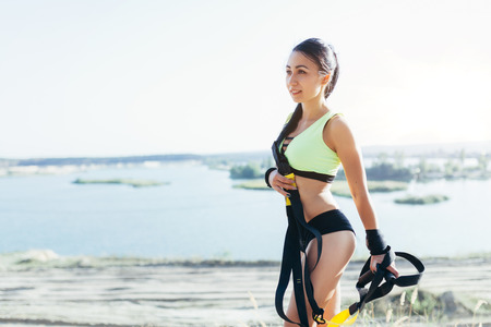 Young attractive woman rest after suspension trx training with fitness straps outdoors in the nature
