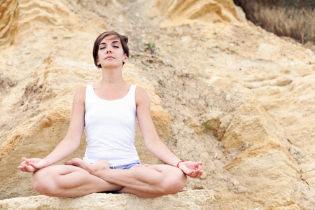 Foto de A beautiful young girl with short hair is dressed in shorts and a white jersey is practicing yoga on the background of rocks. Pose of the lotus. The concept of calm and concentration. - Imagen libre de derechos