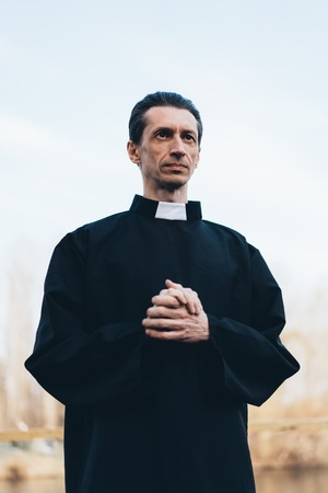 Photo pour Portrait of handsome catholic priest or pastor with collar Standing outdoors - image libre de droit