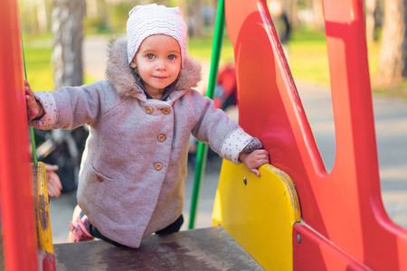 Foto de little cute girl playing at the playground in autumn Dressed in the gray fashionable coat - Imagen libre de derechos