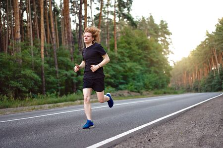 Foto de Caucasian young curly blonde man athlete runs sunny summer day on  asphalt road in the pine forest. Men 20s years jogging at the nature. training for marathon run. Healthy lifestyle concept. - Imagen libre de derechos