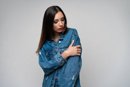 Beautiful caucasian girl denim jacket posing in studio on white background. Seductive brunette. Denim fashion red lips elegant make up. Young adult woman standing indors with sad face emotins