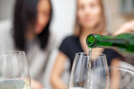 A male hand in the foreground pours wine into glasses. There are two female figures in the background. Friends meeting. Two unrecognizable girls drink wine in the home kitchen.