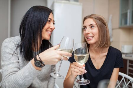 Photo pour Friends meeting with wine and cake in the modern style kitchen. Young women smile and joke with glasses of wine in his hands. Two girls drink wine in the home kitchen. - image libre de droit
