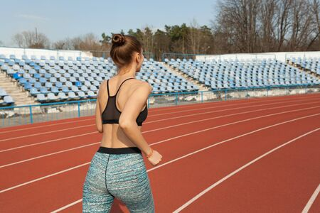 Photo for Young woman running during sunny morning on running track. Healthy lifestyle concept. Weight loss exercising - Royalty Free Image
