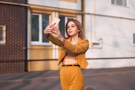 Photo for Beautiful young Caucasian girl 20 years old with white hair dressed stylish orange business suit makes selfie on the phone while standing on the street. Fashion blogger takes pictures of himself - Royalty Free Image