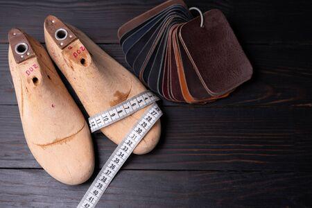 Photo pour Leather samples for shoes and wooden shoe last on dark wooden table. Designer furniture clothes. Shoe maker workspace. - image libre de droit