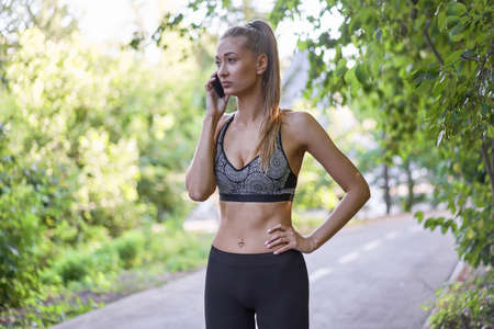 Photo for Woman runner standing before exercising summer park morning Middle age athletic female warming up body before running Caucasian person Talking on the phone. running track - Royalty Free Image