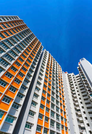 A vertical low angle shot of a new colorful high rise apartment against the sky