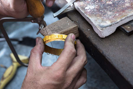 Close up of Jeweler crafting golden bangle with flame torch.