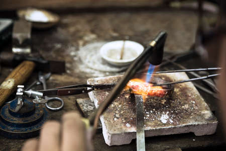 Close up of Jeweler crafting golden rings with flame torch.