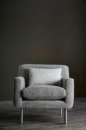 Photo pour Shot of grey color armchair with pillow on hardwood floor - image libre de droit