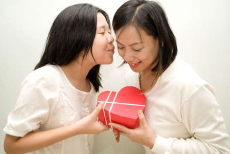 Daughter passing gift to mum and kissing her