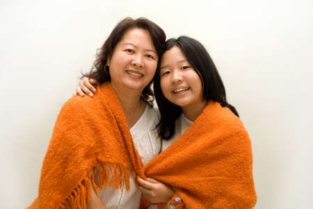 Mother and daughter wrapped in orange blanket