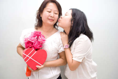 asian girl kissing mum with gifts