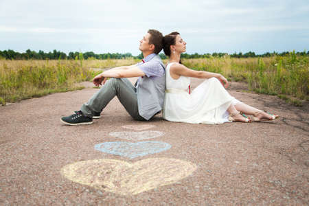 wedding couple sitting on ground. love symbols on pavemant . hearts. people in love. happy bride and groom portraits. man and woman sitting back to back outside on road. newlyweds. wedding day