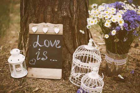 Foto de Love is - inscription for wedding. Wedding decor. Image toned in retro style. - Imagen libre de derechos